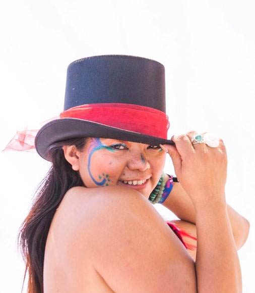 arts facilitator diia bourke appointed 2019. wearing top hat with red band.smiling, with painted face.